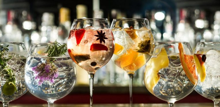 Glasses of gin with fruit, flowers and herbs